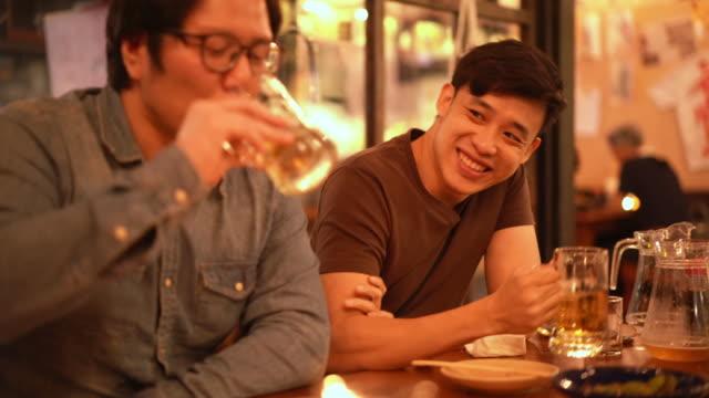酒を飲んで居酒屋の日本居酒屋で話す2人のアサイン男性の3ショット - アルコール飲料点の映像素材/bロール