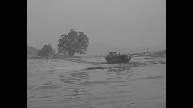 vidéos et rushes de three shots of us marines driving amphibious vehicles across han river / marine drives amphibious vehicle onto land / same vehicle driving down road... - véhicule amphibie
