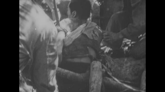three shots of us soldiers capturing japanese soldier dragging him out of underground bunker / note exact month/day not known - 防空壕点の映像素材/bロール
