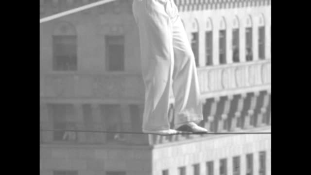 """three shots of volney lafayette """"bunny"""" dryden with wife on his shoulders walking across tightrope / overhead shot of crowd below watching / dryden... - tightrope walking stock videos & royalty-free footage"""