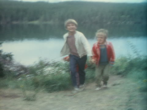 vidéos et rushes de three siblings hold hands and skip near a lake. - frère