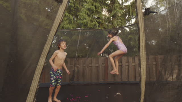 three siblings in their swimsuits jump and bounce around on their outdoor trampoline in the backyard - barefoot stock videos & royalty-free footage