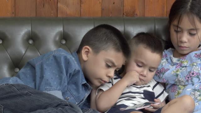 vídeos y material grabado en eventos de stock de tres hermanos ver teléfono inteligente - de lado a lado