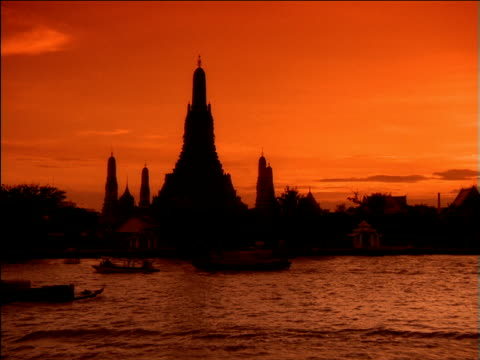 Three silhouetted boats pass each on river passing Wat Arun temple, Bangkok