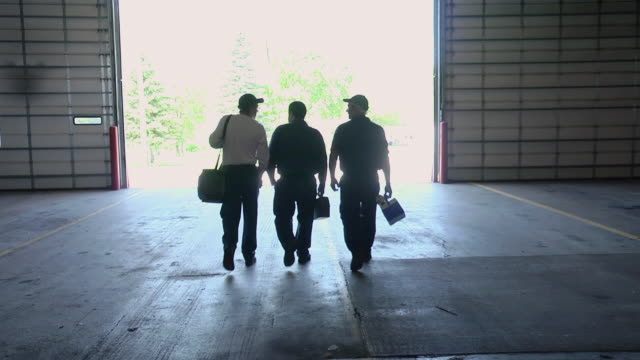 ms slo mo three silhouetted workers walking away / chelsea michigan, united states - manual worker stock videos & royalty-free footage