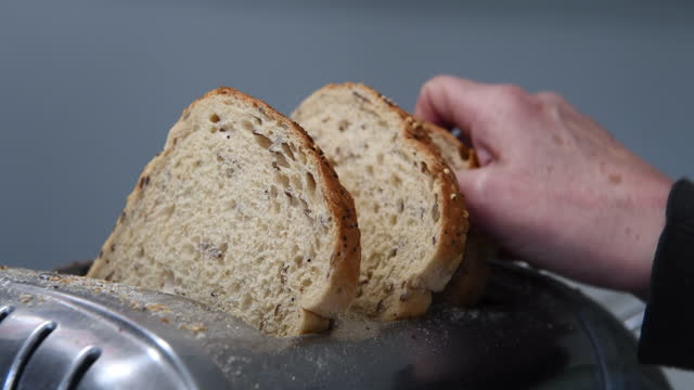 three slices of brown bread being placed in a stainless steel toaster - small group of objects stock videos & royalty-free footage