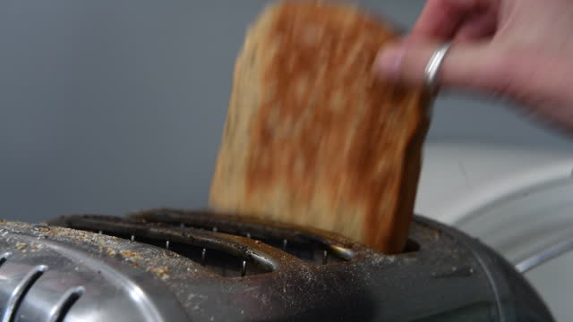 three slices of brown bread in a stainless steel toaster - small group of objects stock videos & royalty-free footage