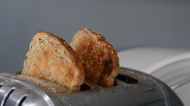 three slices of brown toast popping out of a stainless steel toaster - small group of objects stock videos & royalty-free footage