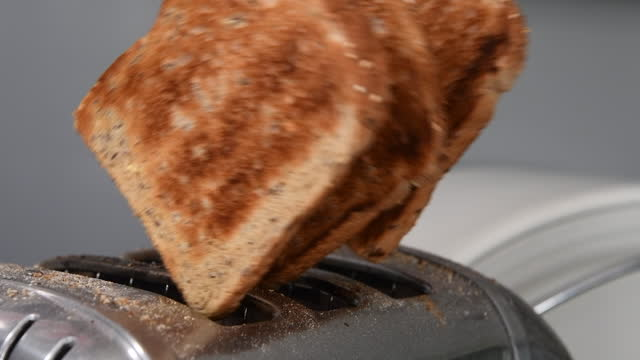 three slices of brown toast popping out of a toaster in slow motion - small group of objects stock videos & royalty-free footage