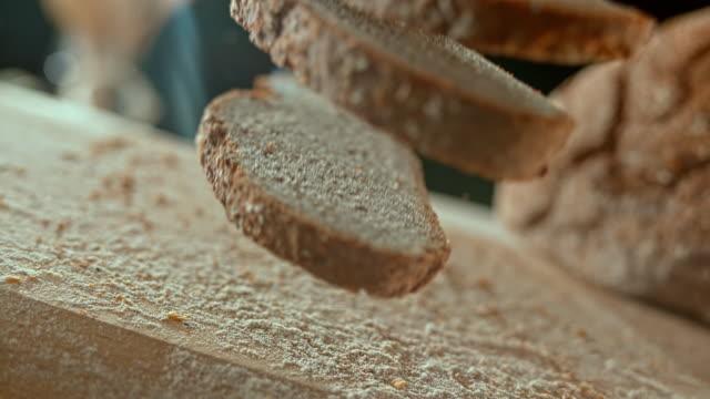 vídeos de stock e filmes b-roll de slo mo ld three slices of rye bread falling on the table - pão
