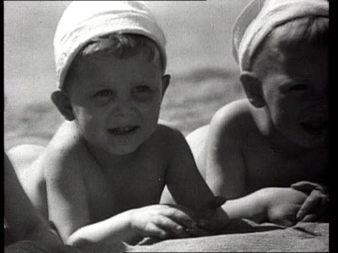 three small boys lying side by side on beach/ ms children playing with watermelon on sand/ ms young girl holding beachball in sea/ ms small boy... - solo un bambino maschio video stock e b–roll