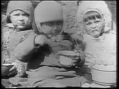 stockvideo's en b-roll-footage met b/w 1921 three small children in coats eating outdoors in winter / russia / newsreel - 1921