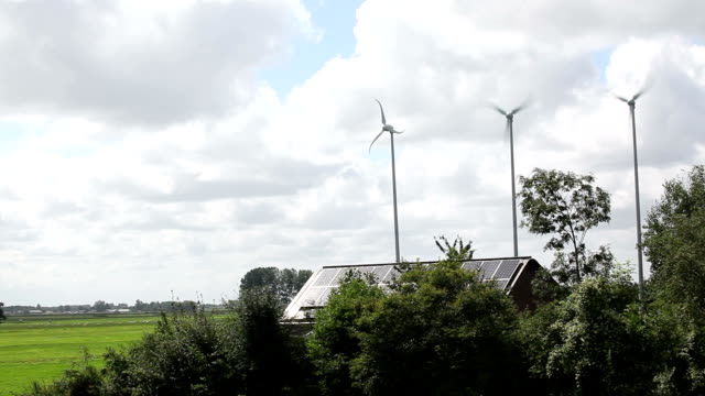 Three small windmills and solar panels on farm house