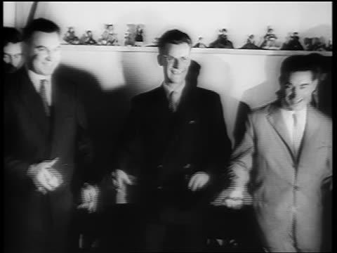 B/W 1961 three smiling men in suits dancing the Twist on dance floor / newsreel