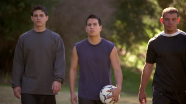 Three soccer players walking side by side towards camera / tilt down one man holding soccer ball
