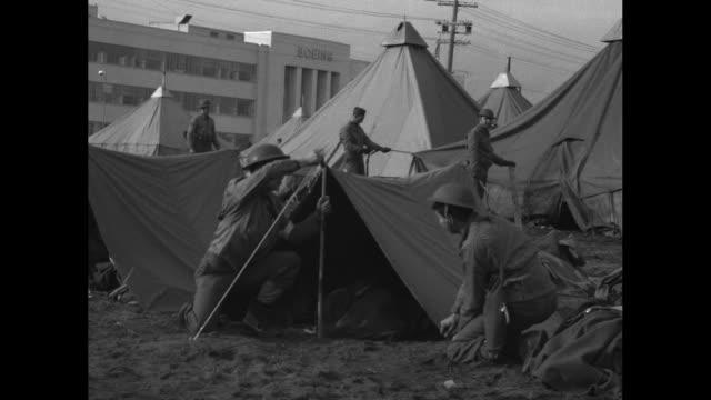 vídeos de stock, filmes e b-roll de three soldiers on guard in front of boeing aircraft factory / vs soldiers camping in tents in front of factory / three shots of school children, many... - world war ii