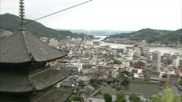 a three story pagoda towers above onomichi as a ship sails toward the onomichi ohashi bridge. - onomichi hiroshima stock videos and b-roll footage
