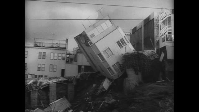 a three story residential building teeters on the edge of a large sink hole caused by a recent earthquake / building falls into the hole / building... - collapsing stock videos and b-roll footage