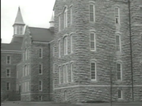 three story stone institutional building group of long windows covered by interior security bars fortress prisonlike mental hospital illness... - psychiatric hospital stock videos and b-roll footage