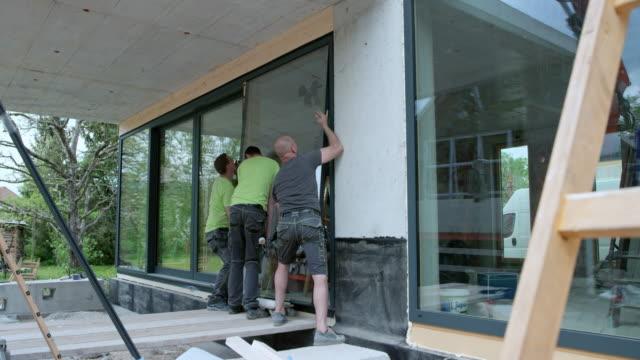vidéos et rushes de trois travailleurs de sexe masculin fortes, plaçant une grande vitre dans le cadre - classe ouvrière