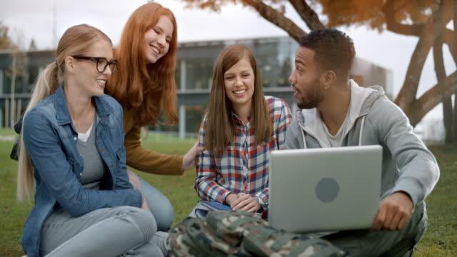 drei studenten gruß ihre freundin kaukasischen verbindenden im park - braun stock-videos und b-roll-filmmaterial