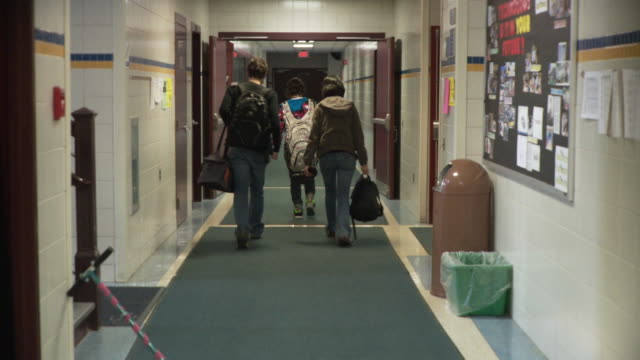 ws three students (15-16) walking down school corridor, cazenovia, new york, usa - male with group of females stock videos & royalty-free footage