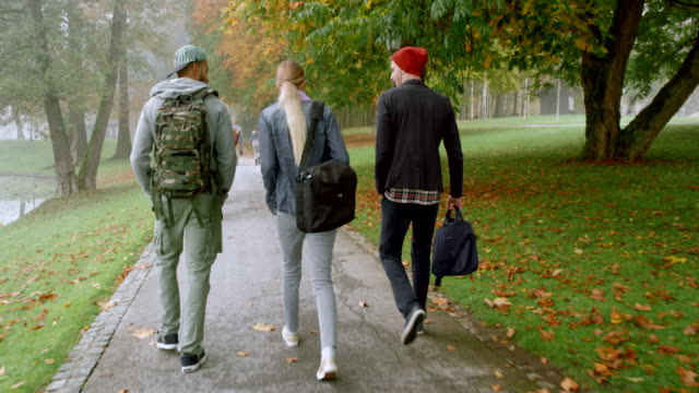 vídeos de stock e filmes b-roll de three students walking through a park on a foggy autumn morning - mochila saco