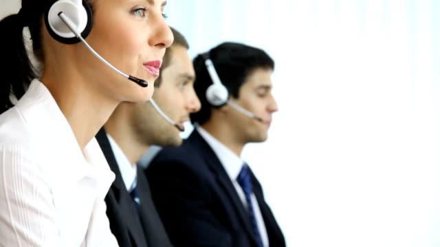 vídeos y material grabado en eventos de stock de tres operadores de teléfono de asistencia en el lugar de trabajo - centro de llamadas