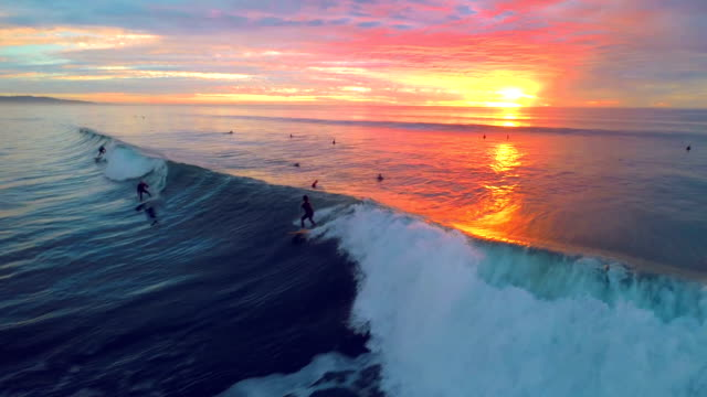 Three surfers on one wave drone view during sunset