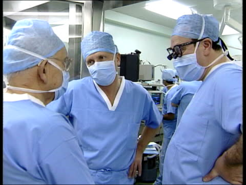 three surgeons standing chatting in operating theatre in masks scrubs - scrubs stock videos & royalty-free footage
