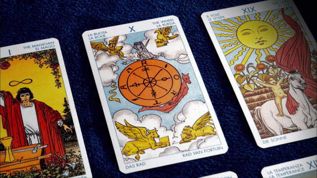 three tarot cards lie on a blue surface. - tarot cards stock videos & royalty-free footage