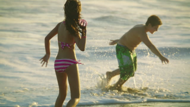 Three teen age children engaging in a water-balloon fight on the beach in slow-motion with the ocean surf behind them.