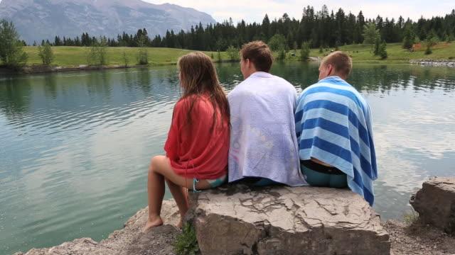 three teen friends relax at edge of mountain lake, chatting - タオルにくるまる点の映像素材/bロール