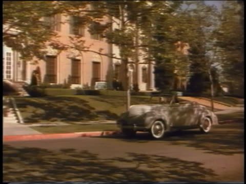 1939 pan three teen girls drive convertible ford past large building in suburbs - 1939 stock videos and b-roll footage
