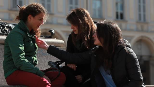 Three teen  girls have conversation on stairs, urban piazza