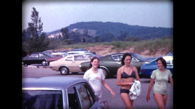 1974 three teen girls in bathing suits in parking lot