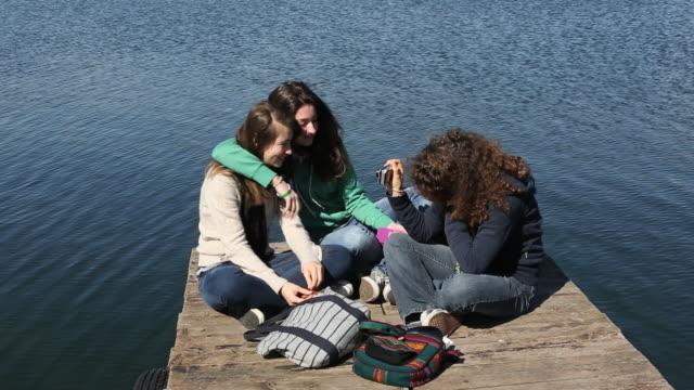 three teen  girls take picture on pier, mountain lake - meraviglie della natura video stock e b–roll