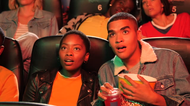 three teenagers glued to screen in movie theatre, close up - weekend activities stock videos & royalty-free footage