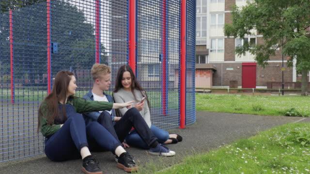 stockvideo's en b-roll-footage met drie tieners opknoping out in het park op hun mobiele telefoon - public park
