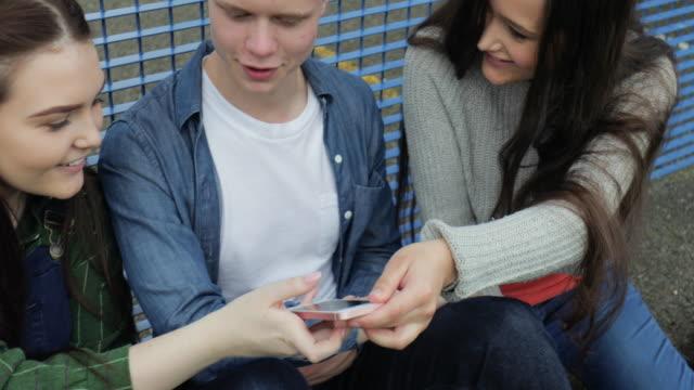 drei teenager hanging out auf handy - drei personen stock-videos und b-roll-filmmaterial