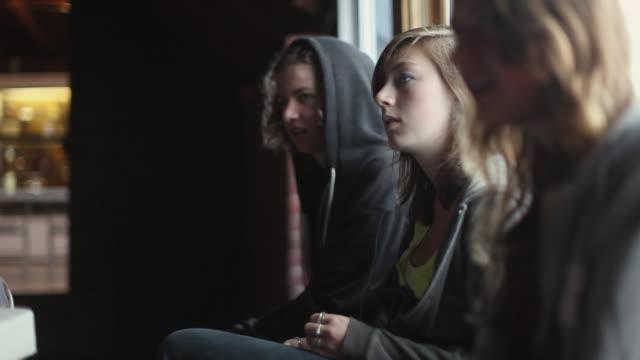 MS SELECTIVE FOCUS Three teenagers (14-15, 16-17) sitting on window ledge and talking / Cazenovia, New York, USA