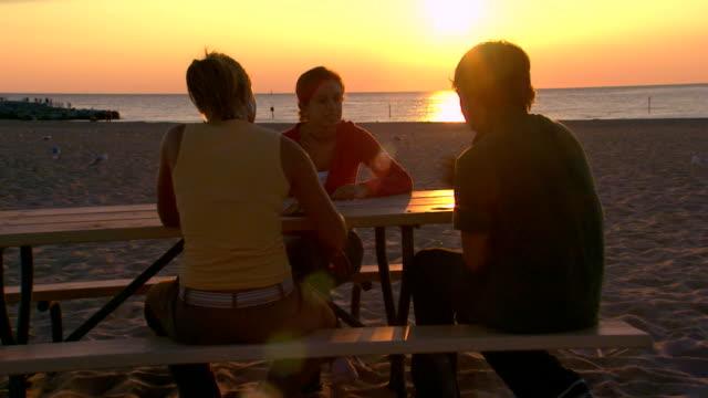 Three teens playing cards at a picnic table at the beach