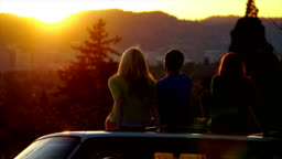 Three Teens Sit On Car And Watch The Sunset Together