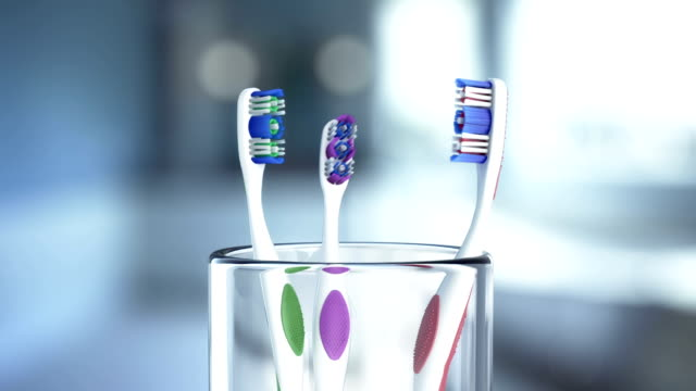 three toothbrush in glass rotating - toothbrush stock videos & royalty-free footage