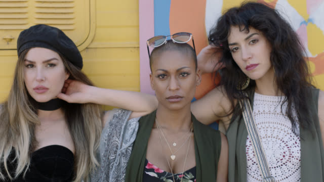 vidéos et rushes de slo mo. three tough young women stare at camera in front of colorful background. - regarder fixement