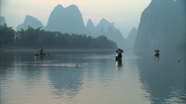 stockvideo's en b-roll-footage met ws, three traditional cormorant fishermen on li river at dusk, guangxi province, china - cormorant