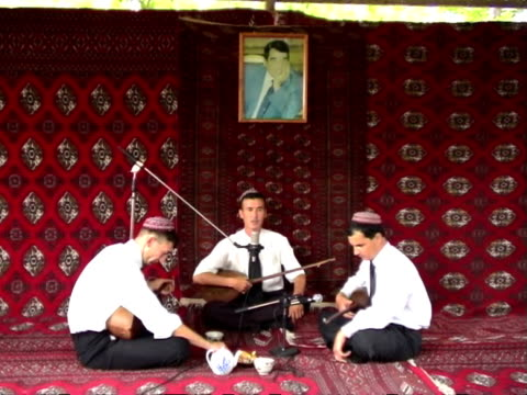 stockvideo's en b-roll-footage met three turkmen musicians on stage covered with local carpets during bakhshi musical contest ashghabad turkmenistan audio - in kleermakerszit