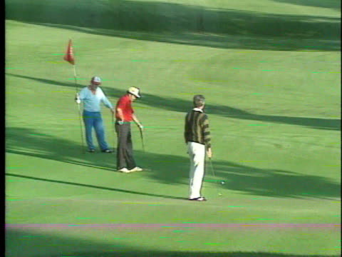 three unidentifiable males playing golf on course, male putting on green, grass covered mountains bg. sports - green di golf video stock e b–roll