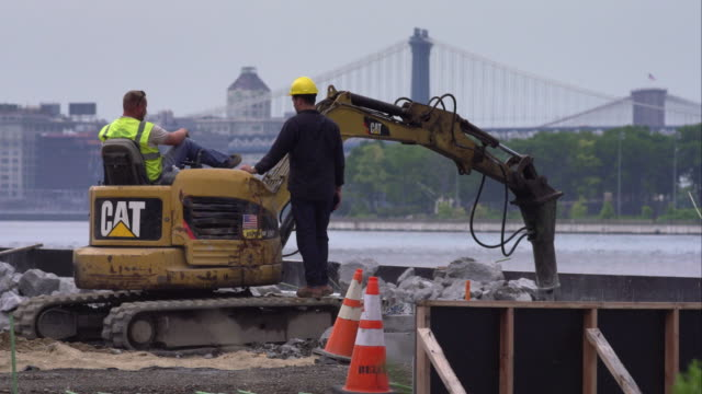 three unrecognizable construction workers take a break at a site along the east river with views of new york city bridges in the distance. - bulldozer stock videos and b-roll footage