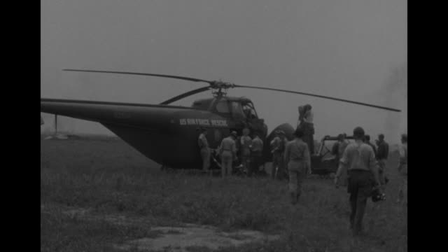 MS three US airmen stand in front and lean on Air Force rescue helicopter / MLS rear view US Air Force personnel and journalists walk toward 'US AIR...
